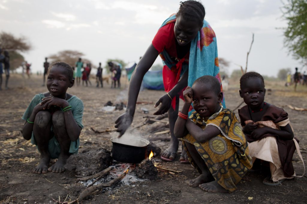 A woman cooks a meal outside in the open air with her three children where she is camping with her family the night before being able to register for a ration card  in Thanyang, South Sudan on March 20, 2016. Nearly 15,000 people from surrounding areas made their way to Thanyang to register for support with Unicef  and the WFP who are running a Rapid Response Mission to support the most in accessible regions affected by the ongoing civil war.  There are no health clinics, bore holes, schools or roads in the area and some people walked for two days to get there. The only water people have access to comes from the swamp. During the Rapid Response Mission (RRM) in Thanyang, Unity State that took place on 18-24 March, WFP and UNICEF teams has provided assistance to nearly 15,000 people. This included providing 1,243 children with OPV vaccine, screening 2,820 children for malnutrition and registering 27 severely malnourished and 357 moderately malnourished children; setting up two new classrooms and registering 900 children for school, setting up a child friendly space for some 730 children and registering 27 separated and 5 missing children. Rapid Response Mechanism (RRM) provides life-saving assistance to children and families affected by conflict, targeting hard-to-reach locations where partners are unable to adequately respond to the immense levels of need. In addition to providing immediate services, the RRM establishes a framework of humanitarian access, which enables partners to establish longer – term presence in disaster – affected locations. Through the RRM, UNICEF provides critical multi-sector emergency response including: health, child protection, education, nutrition and WASH.
