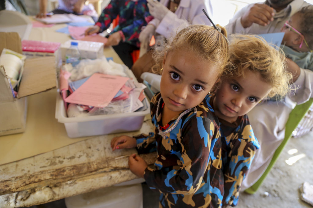 On 15 July, two girls wait in line at a temporary medical centre in Bzebiz Displacement Camp in Baghdad Governorate. With support from UNICEF, WHO, and the Ministry of Health, the medical convoy provided vaccinations and health and nutrition support to vulnerable displaced children in this and other camps in the area. With support from the Ministry of Health, WHO and UNICEF, a mobile medical convoy visits camps for internally displaced families in Baghdad Governorate in order to provide vaccination and health and nutrition support to vulnerable children living in the camps. As part of an ongoing emergency response to the humanitarian crisis in Iraq, from January 2015 through May 2016, UNICEF and partners supported the following health initiatives: Nationwide communication and social mobilization efforts for the oral cholera vaccination and polio campaigns; support to the Ministry of Health and the Directorates of Health to enhance routine immunisations for Syrian refugees and IDPs, along with strengthening health systems in under-served communities; procurement and distribution of cold chain equipment, as well as polio and measles vaccines; a 'baby-hut' initiative that provides breastfeeding counselling to pregnant and lactating women. By July 2016 in Iraq, an estimated 10 million people - including 4.7 million children, or one third of all children in Iraq - were in urgent need of humanitarian assistance, including 3.3 million internally displaced people, returnees, host communities in need, and people in areas under control by or newly liberated from armed groups, as well as 245,000 refugees from the Syrian Arab Republic.