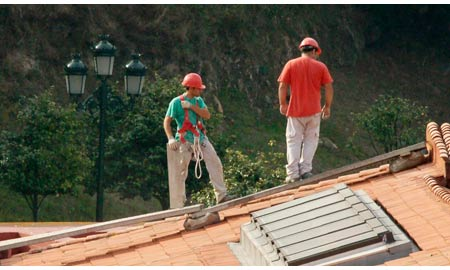 traballadores se arnes nun tellado.
