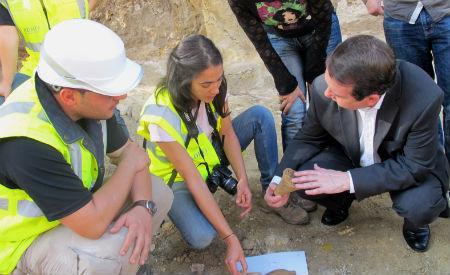 A arqueóloga Eva Albaladejo, xefa da excavación,a,osa ao alcalde varios dos restos atopados
