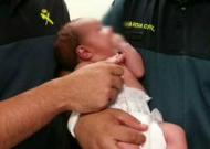 El bebé en brazos de los agentes de la Guardia Civil que lo sacaron de la basura