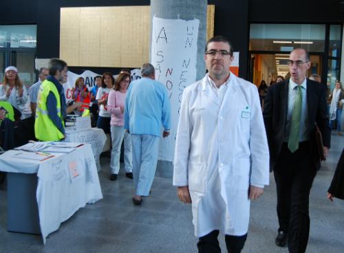 El gerente del Área Sanitaria de Vigo, Félix Ruibal, y el nuevo conselleiro, Jesús Vázquez Almuiña, pasan delante de los celadores acampados en el Álvaro Cunqueiro