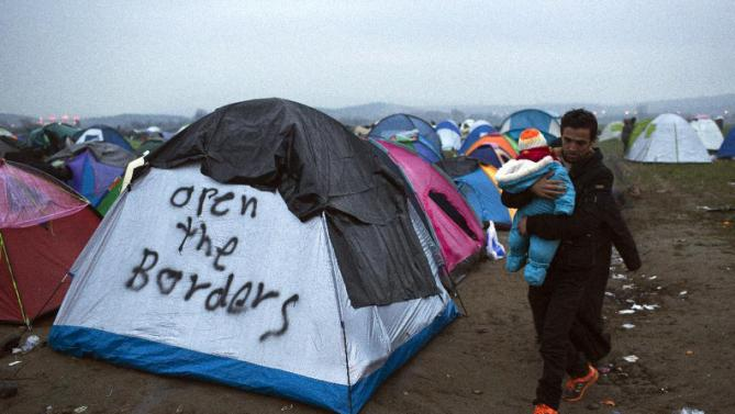 Refugees walk past tents near the Greek-Macedonian border, in the northern Greek village of Idomeni, on Monday, Feb. 29, 2016. Some 7,000 migrants, including many from Syria and Iraq, are crammed into a tiny camp at the Greek border village of Idomeni, and hundreds more are arriving daily. (AP Photo/Petros Giannakouris)