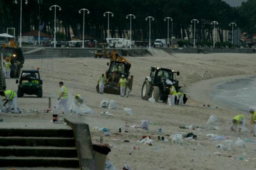 Personal de limpieza retira basura de la arena de Samil este viernes por la mañana