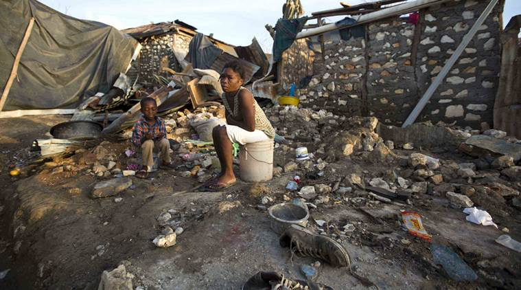 A woman and a child sit on a buckets amid the ruins of their home destroyed by Hurricane Matthew, in Jeremie, Haiti, Monday, Oct. 10, 2016. Almost a week after Matthew's assault, power is still out, water and food are scarce, and officials say that young men in villages along the road between the hard-hit cities of Les Cayes and Jeremie are putting up blockades of rocks and broken branches to halt convoys of vehicles bringing relief supplies. (AP Photo/Dieu Nalio Chery)