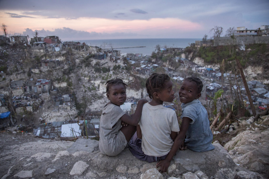 """On 13 October 2016 in Jérémie, Haiti, Mylove Théogène, 8, sits with other girls near her home.  Mylove's family stayed in their home on a hilltop until their home collapsed around 5:00am on the night Hurricane Matthew struck Haiti. Then, the family then moved to a school house for shelter.  """"I thought I was going to die.  I thought my family would all die"""" said Mylove.  The family of five lost their father in February 2016, when he fell from a tree while collecting fruit for the family to eat. """"When I grow up I want to go to school"""" Mylove remarks as a second-grader who has not been to school at all in 2016.  More than one week after Hurricane Matthew, as schools re-open across the country, more than 100,000 children will be missing out on learning after their schools were either damaged or converted into shelters. Hurricane Matthew passed over Haiti on Tuesday October 4, 2016, with heavy rains and winds. While the capital Port au Prince was mostly spared from the full strength of the class 4 hurricane, the western area of Grand Anse, however was in the direct path. The cities of Les Cayes and Jeremie received the full force sustaining wind and water damage across wide areas. Coastal towns were severely damaged as were many homes in remote mountainous regions. International relief efforts are underway to provide food water and shelter to the people affected by the storm. An estimated 500,000 children live in the Grande Anse Department and Grand South Department in southern Haiti, the areas worst hit by Hurricane Matthew.  UNICEF had prepositioned emergency supplies with national authorities to reach up to 10,000 people.  On 8 October, six water trucks arrived in Jeremie and Les Cayes, the respective capital cities within the Departments.  Additional water and sanitation supplies, such as water purification tablets, water bladders and plastic sheeting, have been dispatched to the most affected departments in the westernmost tip of Haiti.  As of 10 October, UN"""