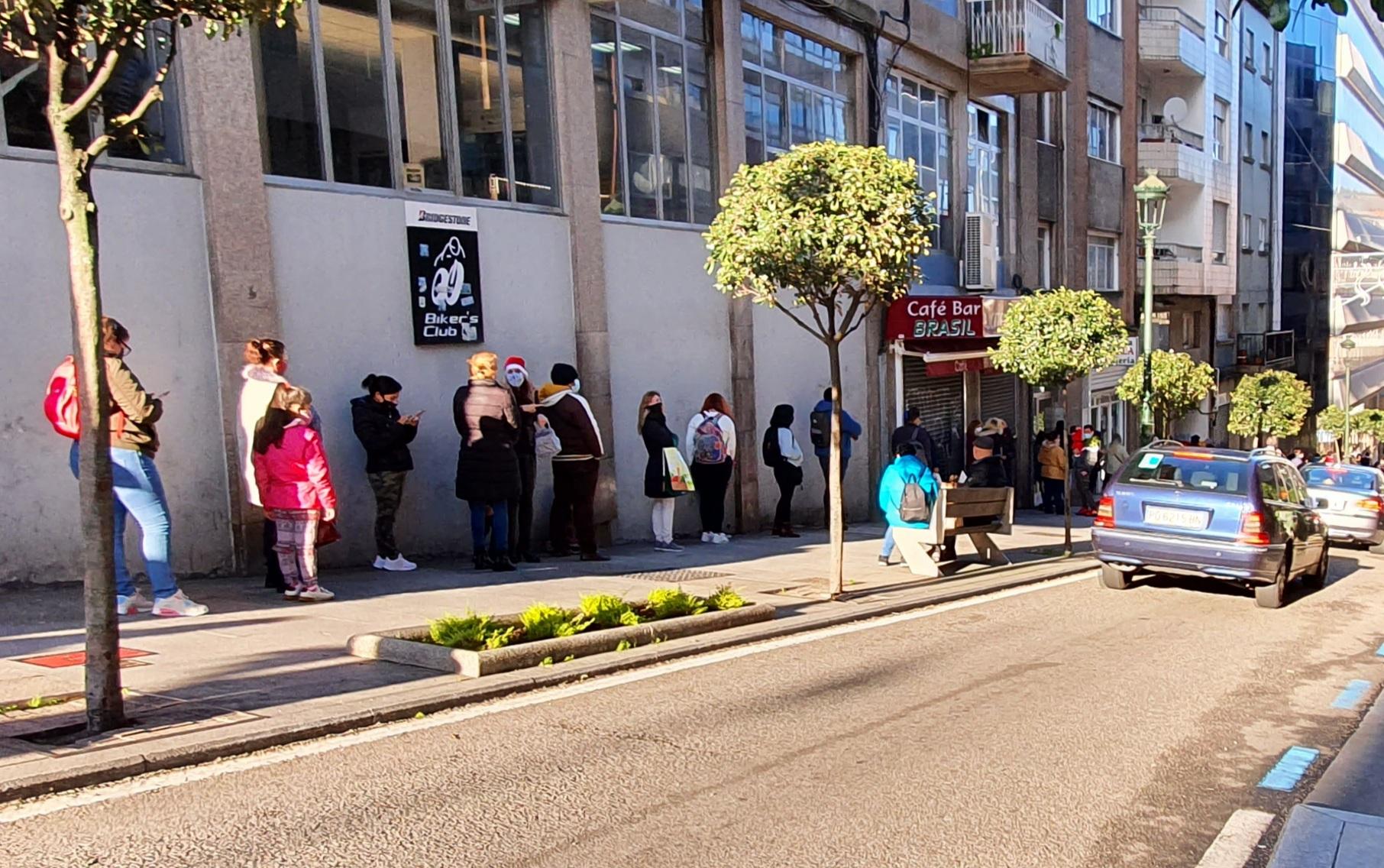 Decenas de personas esta mañana esperando para recoger alimentos en Vida Diga, en la rúa Brasil