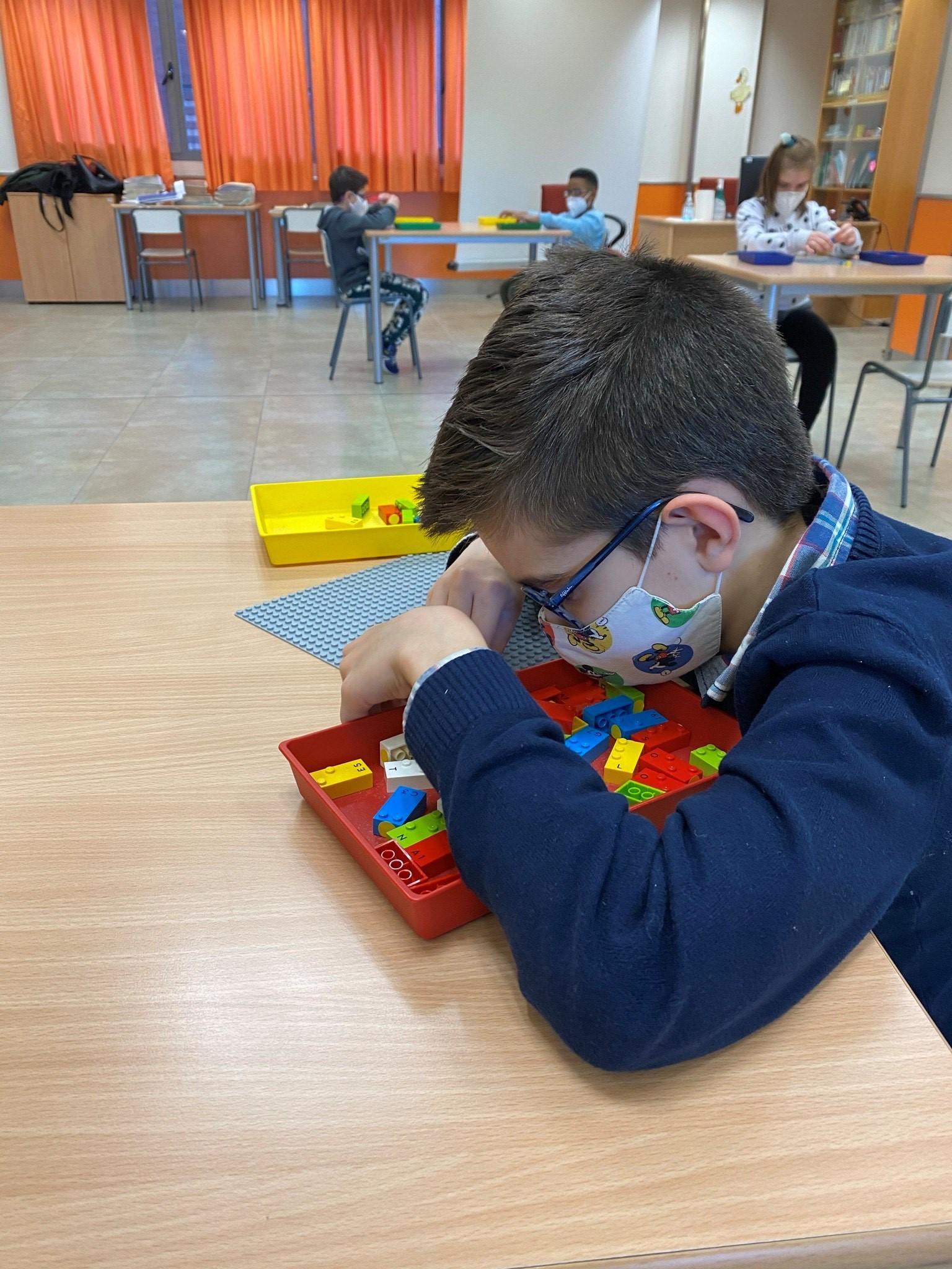 Grupo de escolares jugando en el aula con las piezas de LEGO Braille