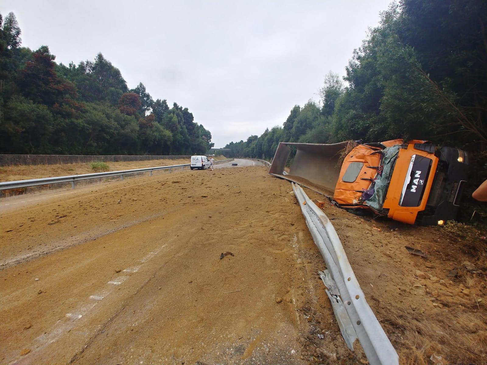 Un camión vuelca pasada la VG-20 dejando gran cantidad de arena en el asfalto